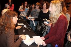 Schülerinnen lassen sich nach der Lesung ihr Buch von der Autorin Maylis de Kerangal signieren